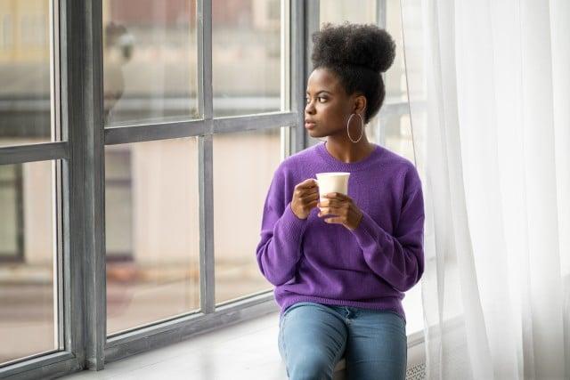 """Frau, die nachdenklich am Fenster sitzt und sich fragt: """"Liebe ich ihn noch?"""""""